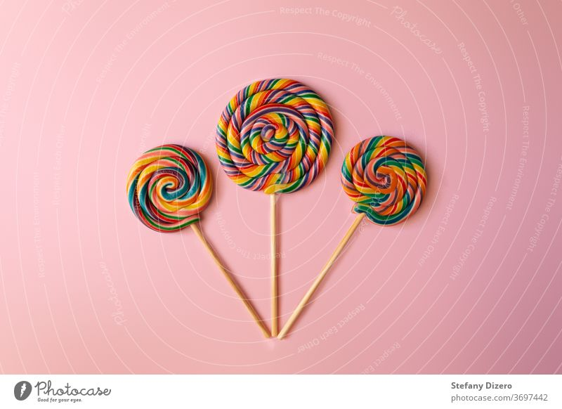 Colorful swirl lollipops arranged on a pink background. birthday candy childhood color colorful cute delicious dessert flat flat design food fun lollypop snack