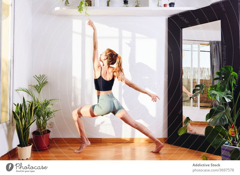 Flexible woman practicing yoga in warrior two pose flexible stress relief asana Virabhadrasana practice female position calm zen wellness meditate harmony home