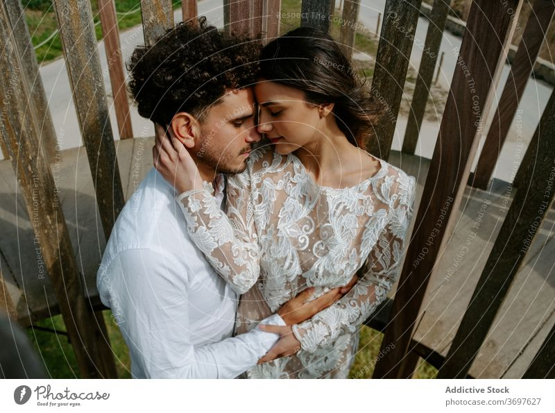 Loving young couple in wedding outfits embracing on bridge romantic newlywed embrace cuddle gentle together relationship love tender marriage sensual hug