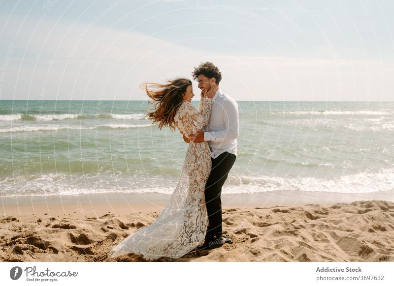 Happy newlywed couple standing against waving sea beach romantic happy cheerful together embrace relationship love nature sand gentle seaside harmony amorous