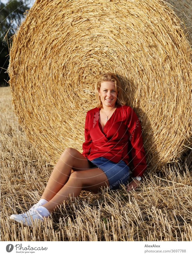 Portrait of a young woman on a bale of straw in the evening light Young woman Woman Blonde smile Red portrait Jewellery already Long-haired Landscape Clouds Sky