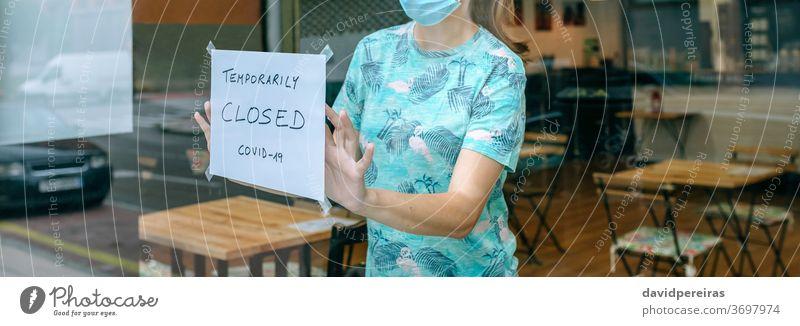 Woman placing coronavirus closure sign woman notice closing covid-19 coffee shop surgical mask sticking poster quarantine banner web header panorama panoramic