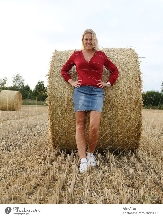 Young woman stands leaning against a bale of straw in the field and smiles Legs free time fun Joy jeans whole body Central perspective Looking into the camera