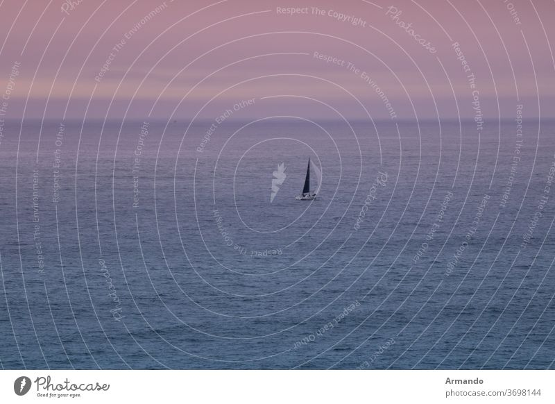 Sailboat sailed only at sunset over the Atlantic Sea outdoor sky background orange beautiful sunlight Purple nature Beam Climate Calm Relax Paradise Mist Dusk