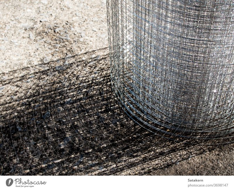 Roll loose shiny thin wire grating grate roll metal steel mesh cage net grid construction texture metallic gray industrial protection security fence