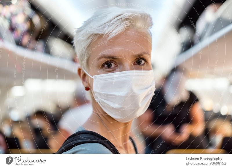 Woman standing in the airplane wearing face mask woman travel traveller aisle corridor interior lifestyle post-covid-19 facemask corona virus safe new normal