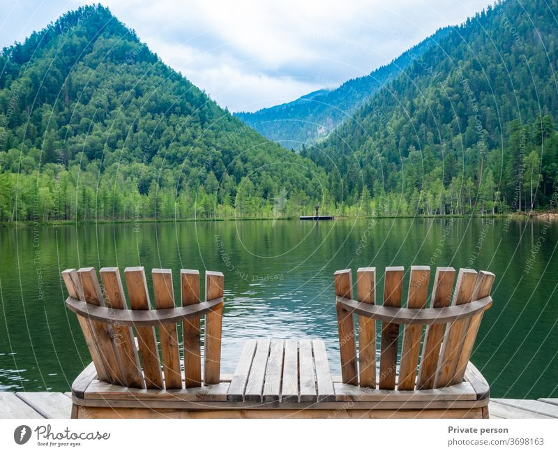 Two empty wooden deck chairs on the beach, beautiful landscape of mountain lake, vacation in the mountains, luxury summer vacation concept. nature calm travel