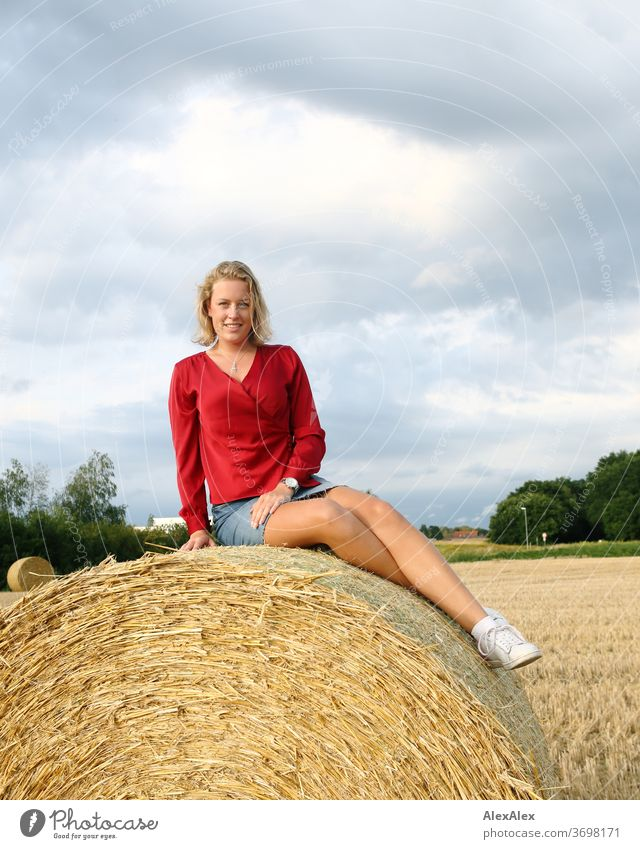 Young woman sitting on a bale of straw in the field and smiling Legs free time fun Joy jeans whole body Central perspective Looking into the camera