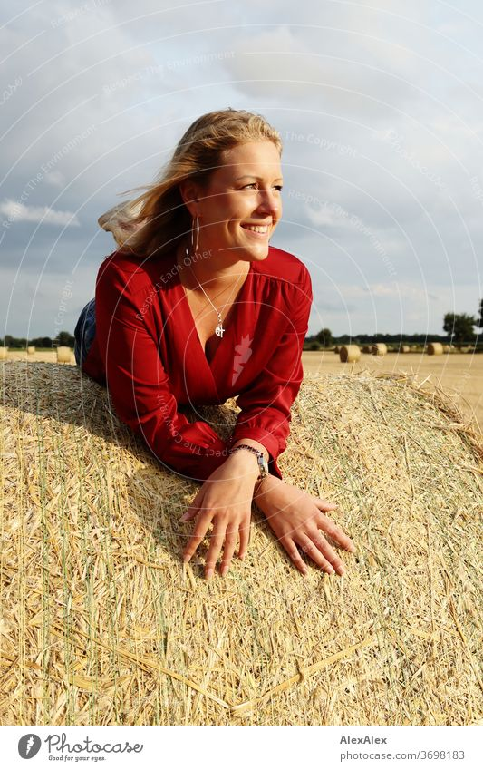 Young woman lies on a bale of straw in the field and smiles free time fun Joy jeans whole body Central perspective Looking into the camera