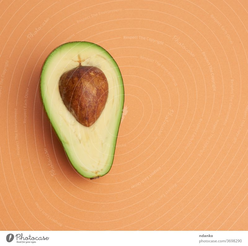 half ripe green avocado with a brown bone on an abstract orange background closeup color creative cut delicious diet dieting eating exotic food fresh freshness
