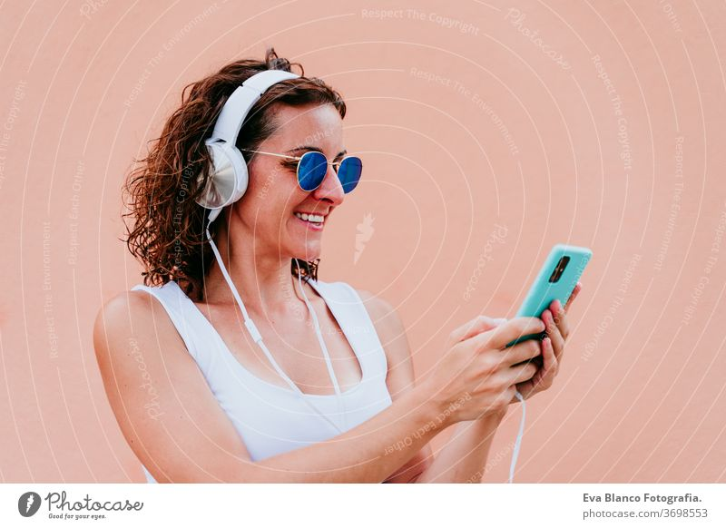 young happy woman outdoors listening to music on headset and mobile phone. Lifestyle at the city. Summertime. close up view music headset urban sunglasses