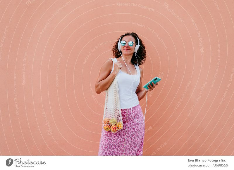 woman using mobile phone, listening to music on headset. walking by the city with cotton bag with fruit. Eco friendly, zero waste concept eco friendly shopping