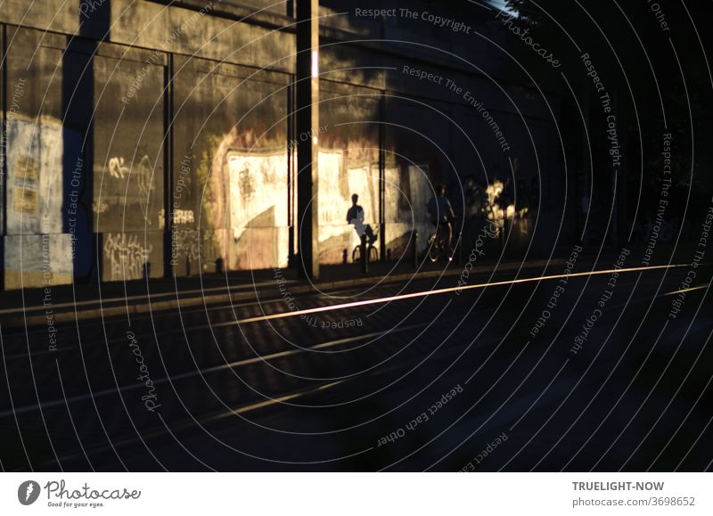 A cyclist disappears into the darkness next to the flashing railway tracks, but the low evening sun casts its sporty shadow on the concrete wall illuminated by the last rays of the sun