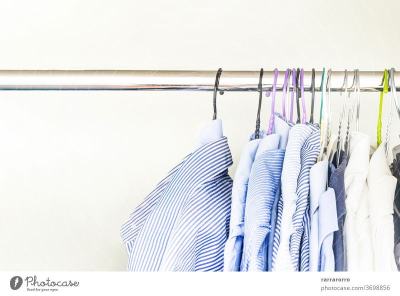 A group of men's shirts of various colors hung with hangers inside a wardrobe hanging dress cotton fabric striped light blue white bar coat hanger adult fashion