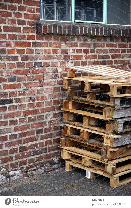 A stack of one-way pallets is standing in front of a building Palett pallet stacks Wall (barrier) built wood Window Workplace Logistics Warehouse
