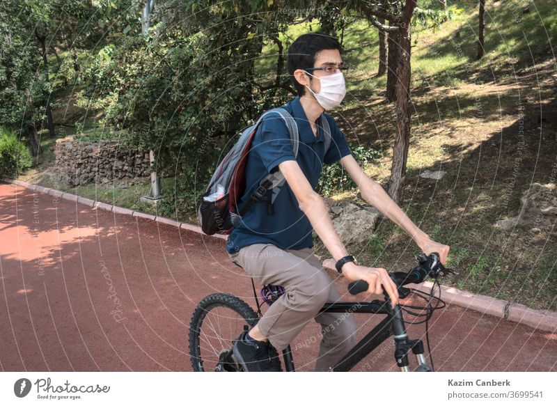 Isolated and masked young male riding a bike at a public park corona coronavirus global epidemic pandemic person man surgical mask bicycle cycling forest