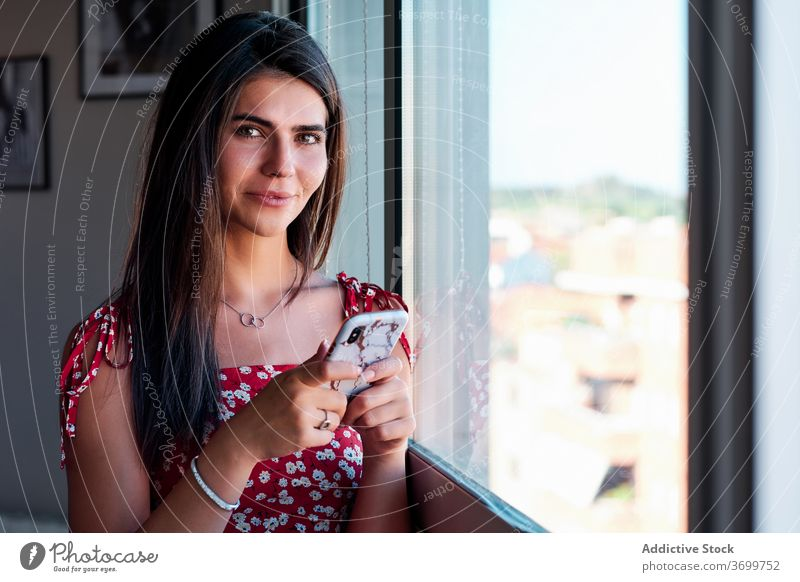 Young woman with smartphone standing near window home using smile brunette casual positive mobile young device gadget browsing message communicate internet
