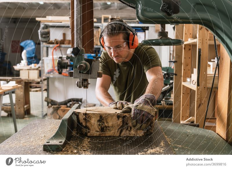 Male woodworker cutting wood in workshop band saw carpenter man professional lumber male timber shabby blade sharp craftsman equipment tool manufacture