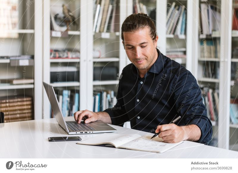 Busy male entrepreneur working on laptop in office businessman typing paperwork busy focus using take note notebook bright workspace executive gadget device