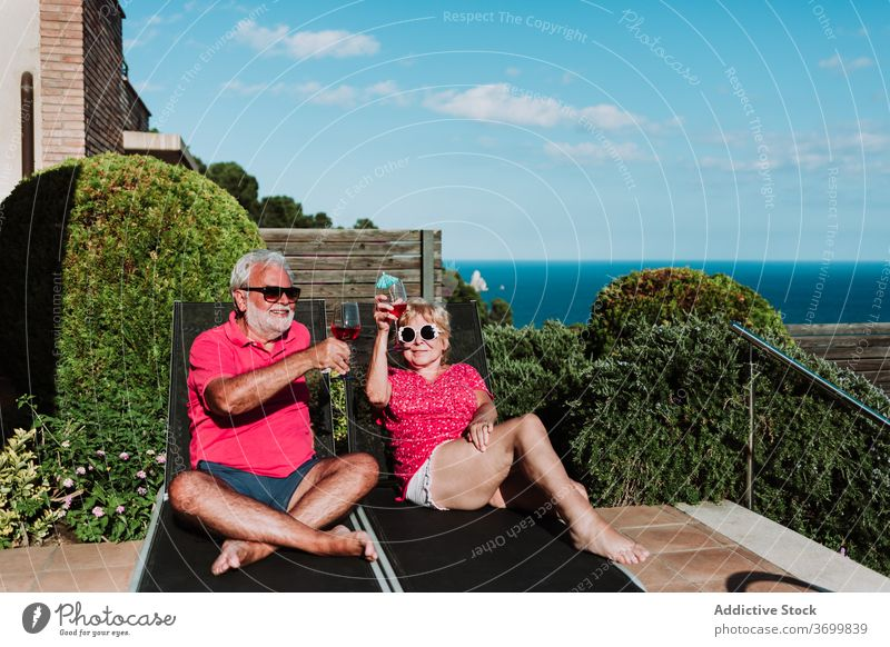 Content elderly couple on deck chairs summer vacation cocktail tropical senior relax together deckchair lying terrace beverage chill enjoy holiday drink