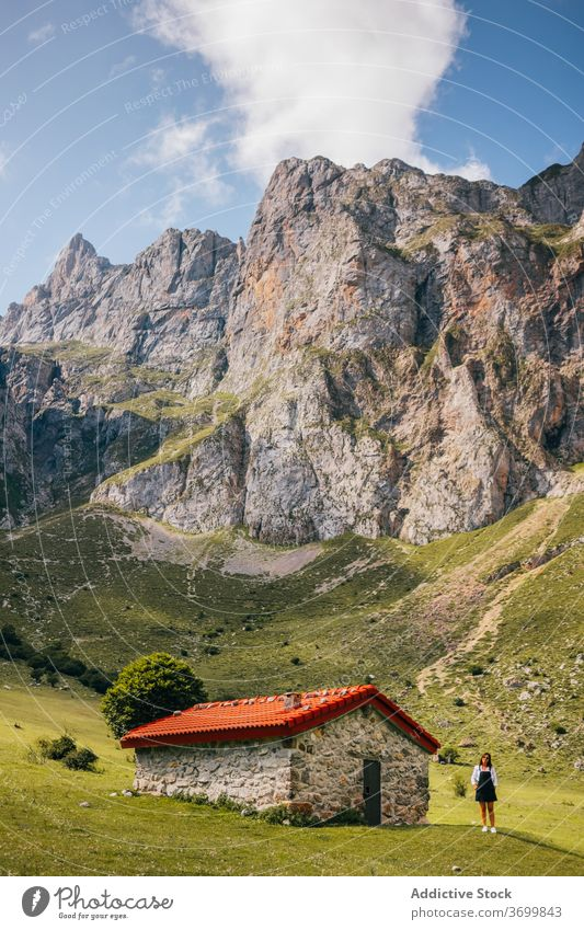 Female standing near stone house in green mountain valley woman range travel residential hiking holiday picos de europa cabin meadow landscape asturias spain
