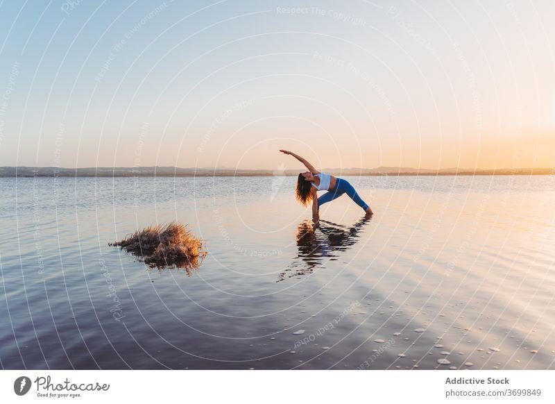 Woman in extended side angle pose reflected in lake water woman yoga practice asana utthita parsvakonasana stand harmony spirit mind grace focus reflection