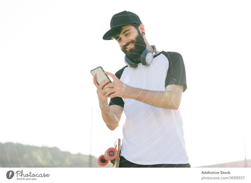 Carefree male skater browsing cellphone in city hipster longboard street man smartphone weekend enjoy using social media piercing content trendy urban relax