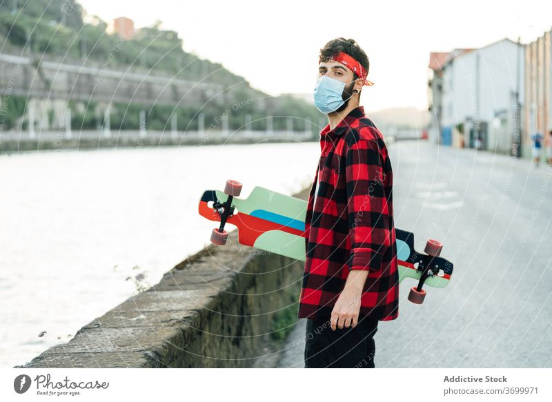 Male hipster in medical mask in city skater longboard promenade man coronavirus walk protect male surgical young summer hobby urban street handsome serious