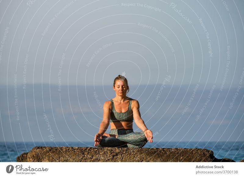 Calm woman doing yoga in Lotus pose lotus pose meditate tranquil mindfulness sea sunset mudra peaceful sundown gesture serene twilight calm harmony zen asana