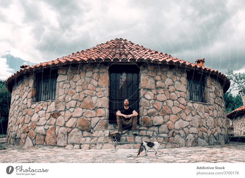 Carefree traveling man near stone building cobblestone city traveler relax stroll vacation summer male aged tourist sit rest old town exterior trip step stair