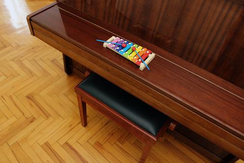 Top view of a toy xylophone and a classical upright piano on wooden flooring in interior shot image. above top stand keyboard colorful black and white real fake