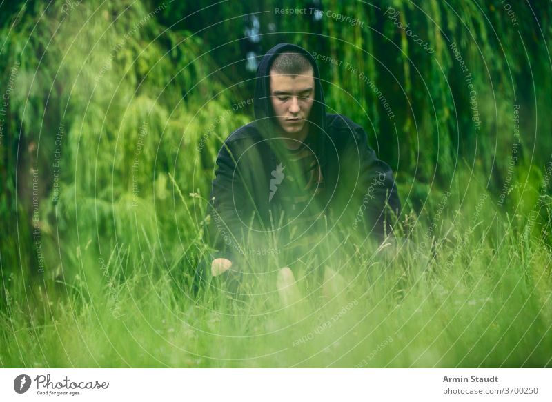 Portrait of a sad, crouching man in a black hoodie portrait young serious worry meadow nature summer look teenager looking male beautiful casual caucasian
