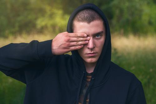 Portrait of a young man with a black hoodie covering his eyes portrait serious hand finger look teenager looking male beautiful casual caucasian outdoor