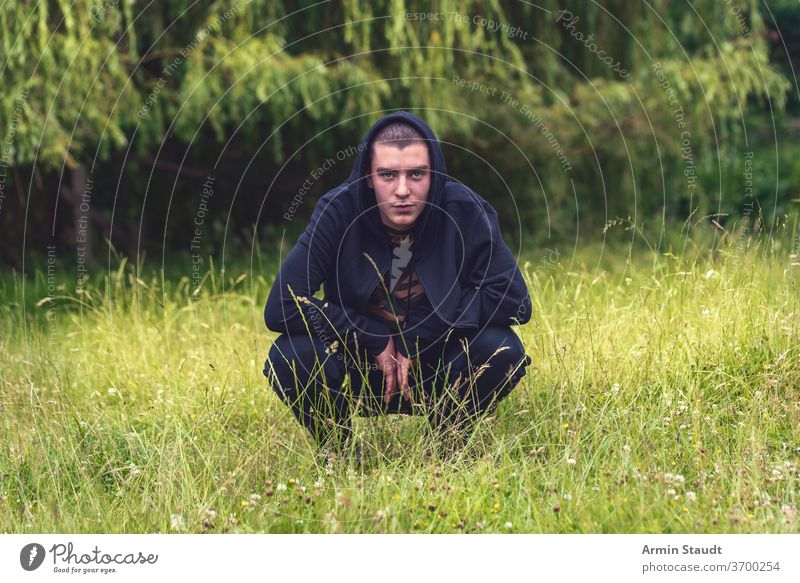 Portrait of a smiling, crouching man in a black hoodie portrait young smile happy lucky meadow nature summer look teenager looking male beautiful casual