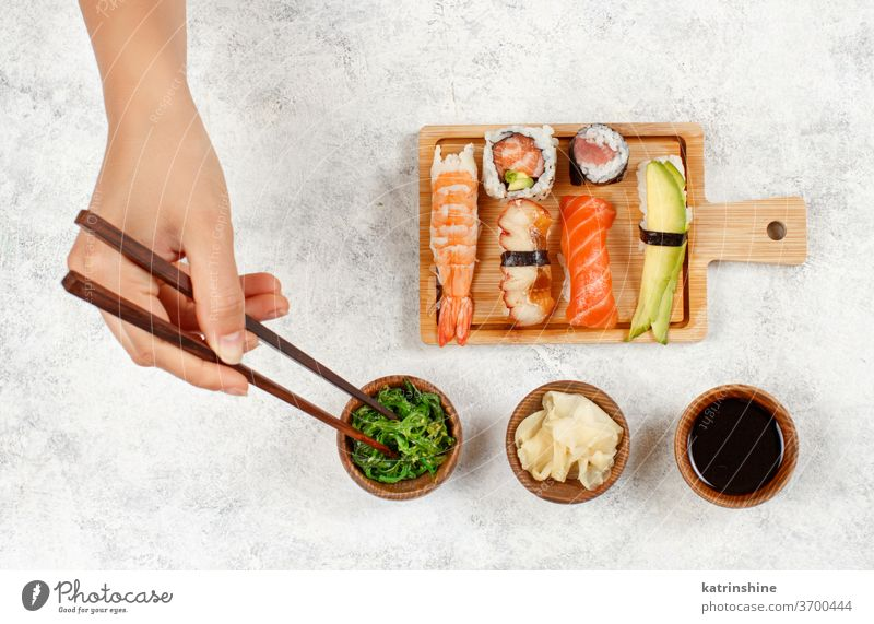 Top view of hand taking roll with chopsticks from a plate sushi ready to eat eating Sashimi Rolls sushi bar dinning Japanese Culture Seafood top view Asian