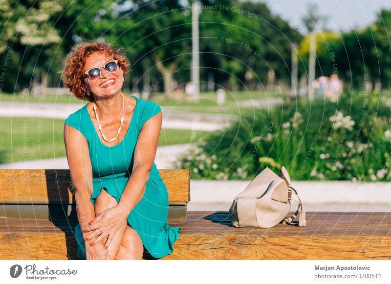 Mature woman sitting on the bench in the park in summertime 60s adult age aged alone beautiful beauty casual caucasian cheerful city confidence confident dress