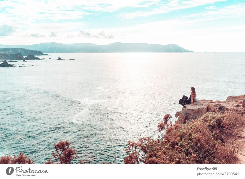 Woman contemplating the ocean from a cliff woman hiking copy space landscape seascape loiba galicia cliffs rocks rocky atlantic tourism spain horizon clean