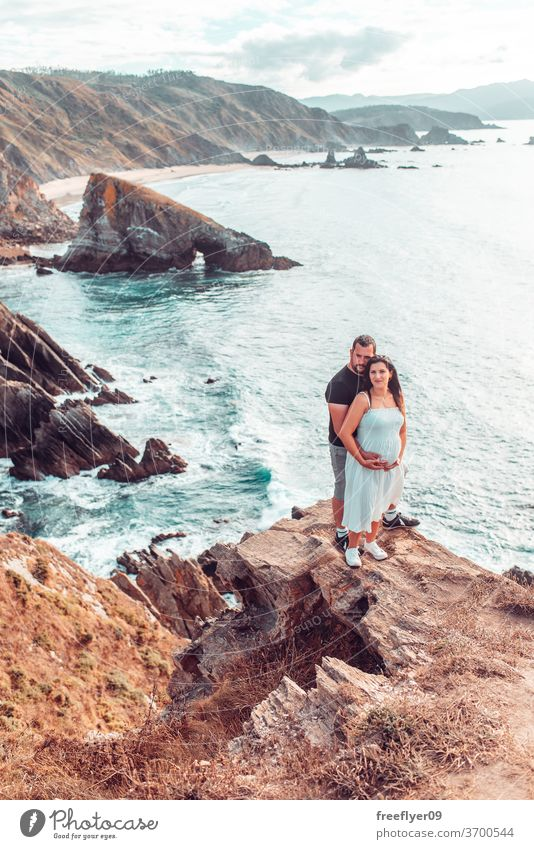 Pregnant couple on the edge of a cliff pregnant heterosexual romantic father mother parents woman contemplating hiking copy space landscape seascape loiba