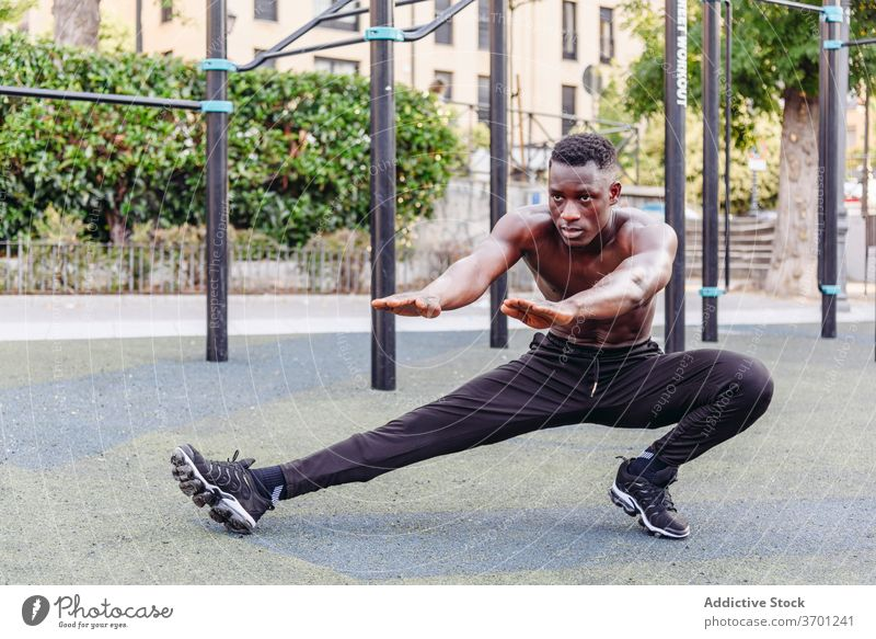 Strong sportsman doing lunges on street exercise training sporty athlete strong workout shirtless muscular sports ground male african american black ethnic