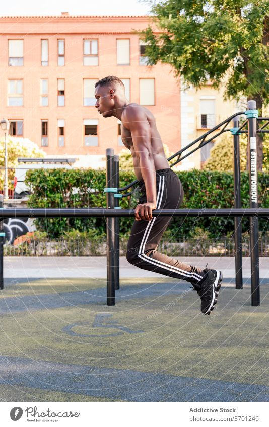 Muscular black sportsman doing pull ups training strong exercise athlete stamina naked torso workout male ethnic african american intense fitness sportswear