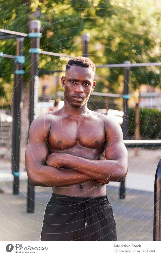 Black male athlete on sports ground sportsman muscular body training relax break determine naked torso ethnic african american black physical power motivation