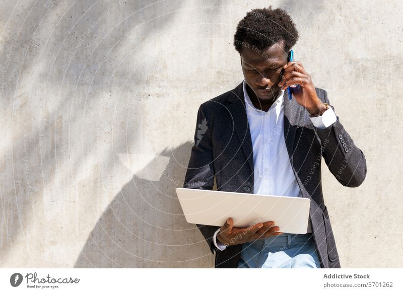 Serious businessman speaking on cellphone in city discuss work smartphone talk manager executive laptop using male ethnic black african american barcelona spain