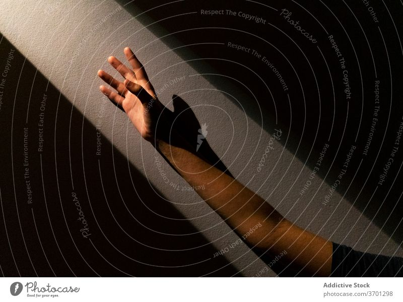 Crop person with outstretched arm reach light dark room freedom concept hope shadow bright sunlight wall stone sunbeam shade stand calm peaceful harmony dreamy