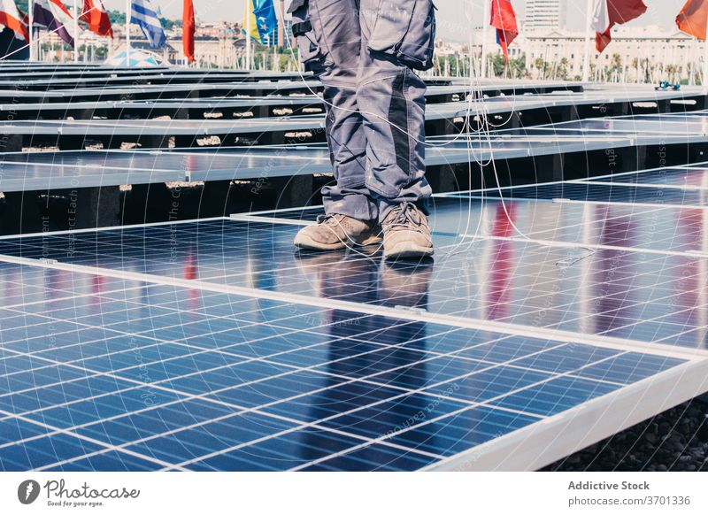 Unrecognizable engineer on solar panel man renewal battery work sustainable industrial energy resource male install alternative power development area plant