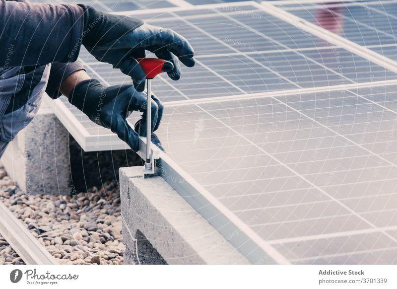 Crop man installing solar panels worker renewal energy alternative sustainable mechanic male screwdriver roof building equipment repair construction power