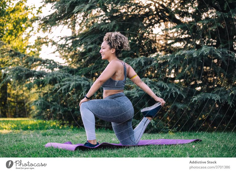 Fit woman stretching legs during training in park exercise lunge fitness sporty cheerful young workout healthy sportswear wellness female ethnic lifestyle