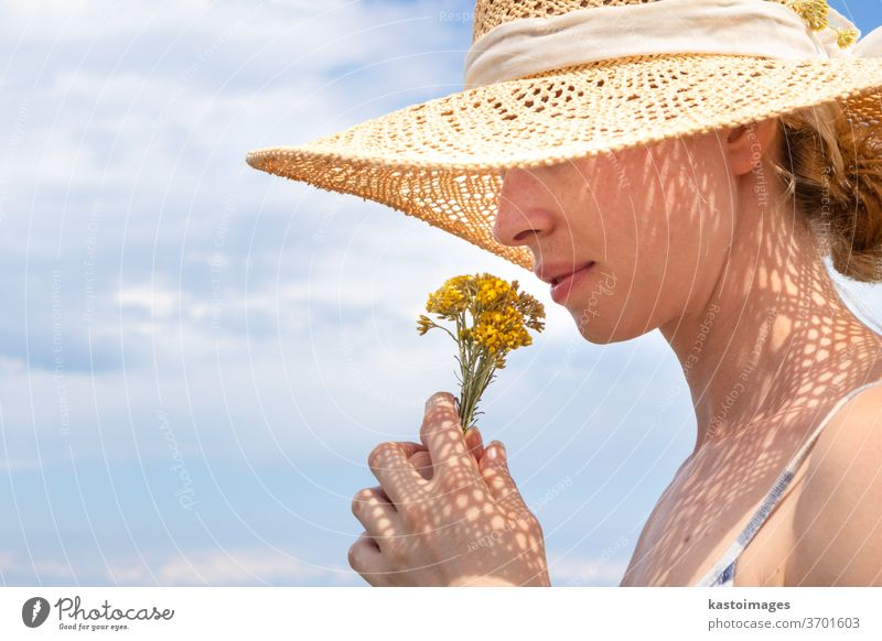 Portrait of young beautiful cheerful woman wearing straw sun hat, smelling small bouquet of yellow wild florets, against blue summer sky portrait flowers scent
