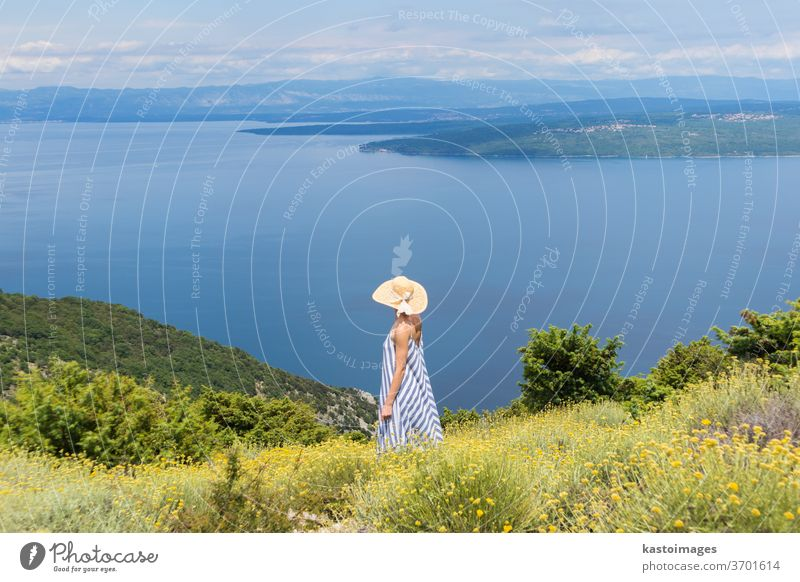 Rear view of a young woman in a striped summer dress and straw hat, standing in a super blossom of wild flowers and relaxing while enjoying a beautiful view of the Adriatic nature, Croatia