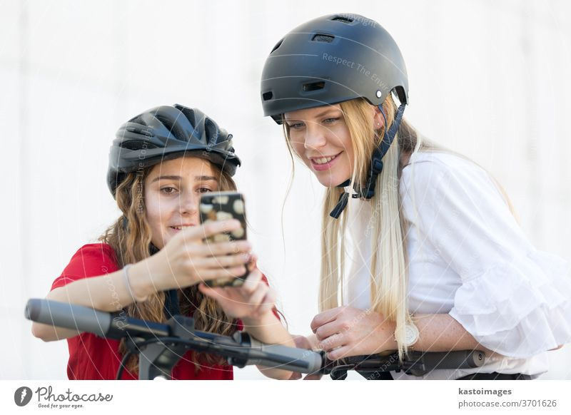 Teenager girls using mobile application to unlock and rent riding public rental electric scooters in urban city environment. Eco-friendly modern public city transport in Ljubljana, Slovenia.