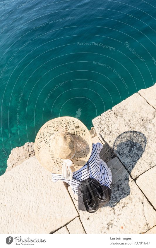 Graphic image of top down view of woman wearing big summer sun hat relaxing on pier by clear turquoise sea. water leisure beauty girl person blue tan body young